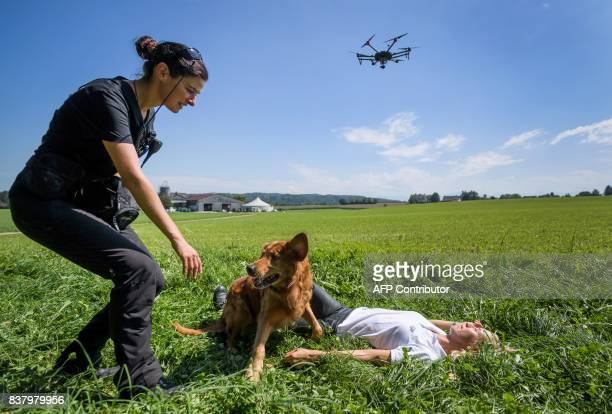 A drone flies as members of Swiss disaster dog association Redog and a rescue dog perform during a press presentation on combined search and rescue...
