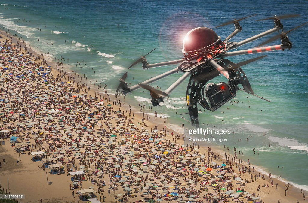 Drone flying and filming over a crowded beach : Stock Photo