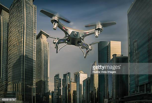 drone flying over a futuristic city - drone stock pictures, royalty-free photos & images