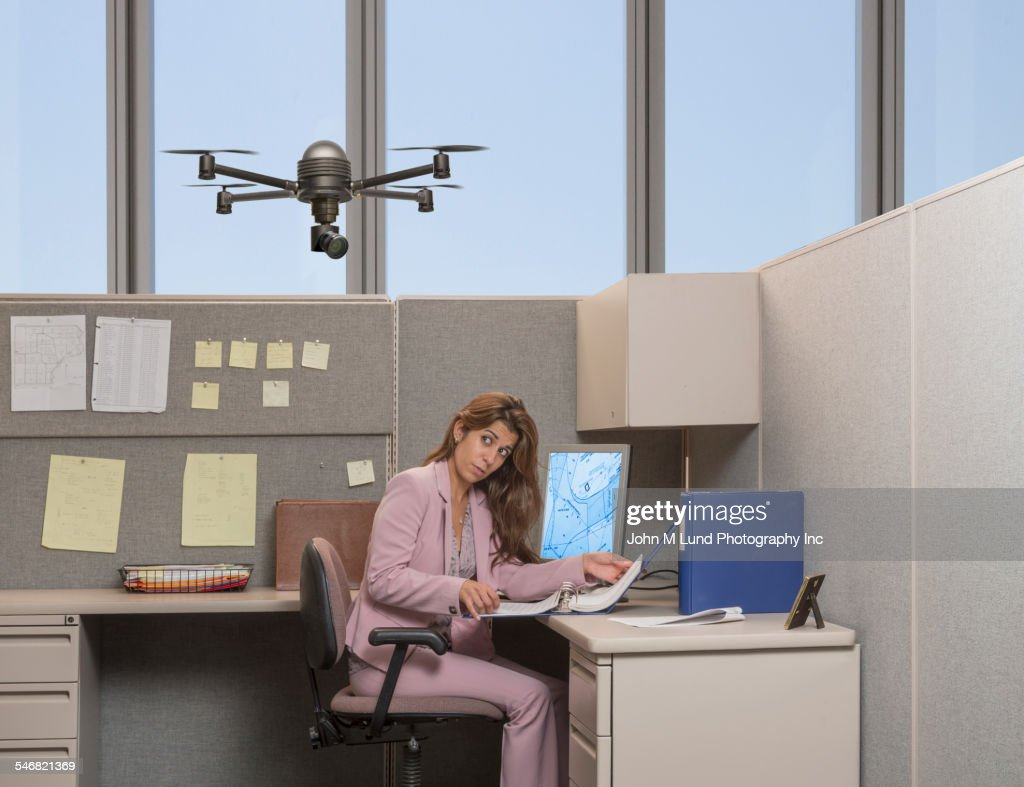Drone hovering over Hispanic businesswoman in office : Stock Photo