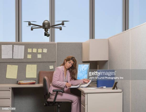 Drone hovering over Hispanic businesswoman in office