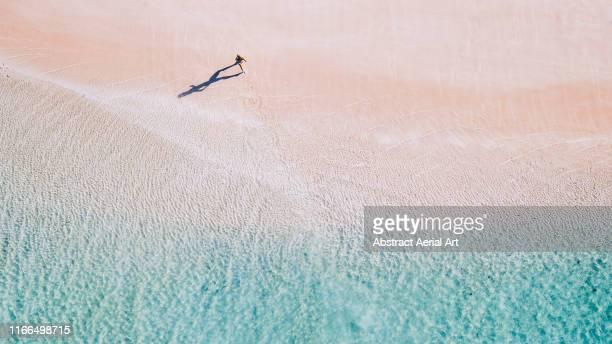 drone image of a girl running along a beach, australia - western australia stock-fotos und bilder