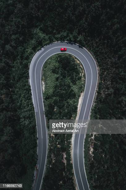 drone image of a hairpin bend in a forest, italy - car on road stock pictures, royalty-free photos & images