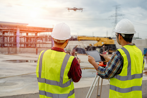 Drone operated by construction worker. 1125525958