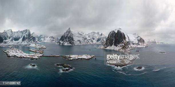 drone panorama landscape of reine and hamnoy fishing villages with fjords and mountains in the background in norway. top view of lofoten islands winter scenery. - north stock pictures, royalty-free photos & images