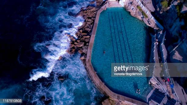 drone photo: bronte beach rock poll - bondi beach stock pictures, royalty-free photos & images