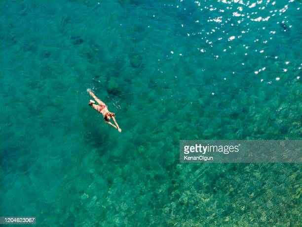 drone photo of woman floating in the sea. - teal stock pictures, royalty-free photos & images