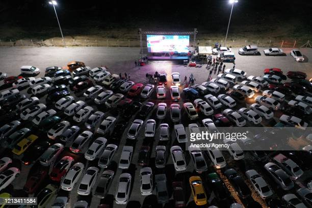A drone photo shows a view of people gathering with their cars to watch the Turkish film Turk Isi Dondurma during the open air cinema event held for...