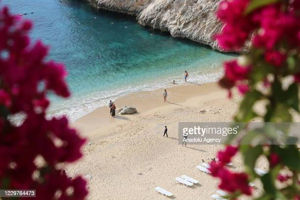Drone photo shows people going in the sea and sunbathing at the Kaputas Beach in the resort town of Kas in Turkey's Antalya province on November 24,...