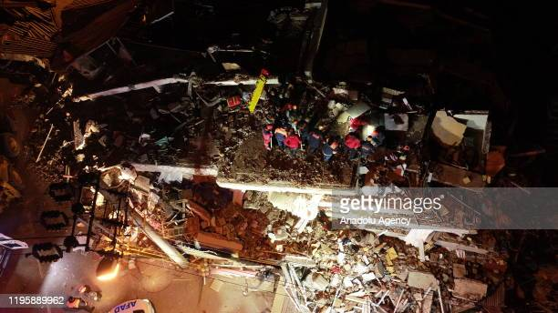 A drone photo shows teams conduct a search and rescue operations for survivors of a collapsed building in Gezin neighborhood of Maden district after...