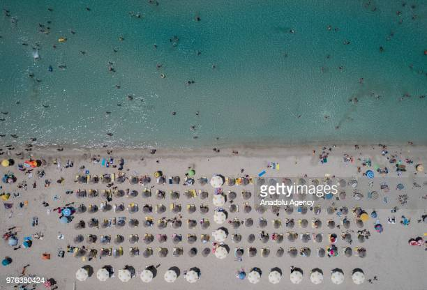 A drone photo shows the aerial view of a beach as people sunbathe under colourful parasols and swim on a summer day at Cesme district during the Eid...