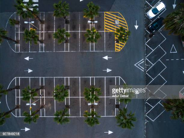 Drone picture taken from directly above with nice parking lot geometry and palm trees.