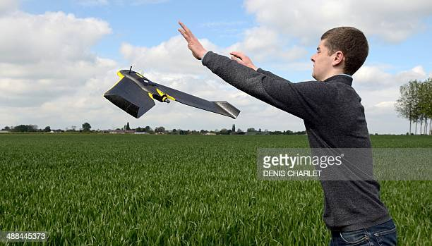 A drone pilot launches a drone plane over a crop field on May 6 2014 in Caulieres northern France during a demonstration of the French Somme...