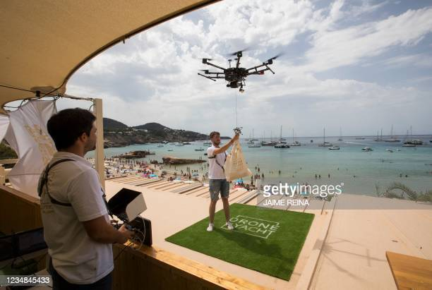 Drone pilot ties up a bag of food to a drone at Cala Tadira near Sant Josep de Sa Talaia in Ibiza Island on August 24, 2021. Drone to Yacht is an...
