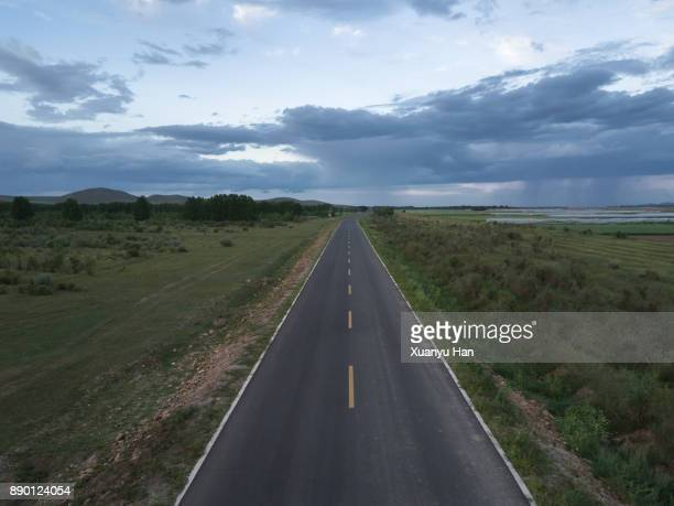 Drone Point of View a long open road stretching out far away into the distance