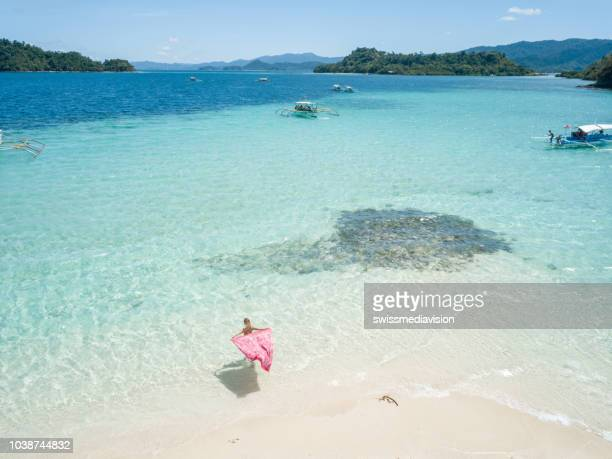 drone point of view aerial view of young woman relaxing on tropical beach, shot in the philippines on remote island. people travel vacations idyllic concept. - palawan stock pictures, royalty-free photos & images
