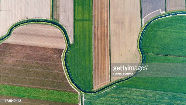 drone point of view of dutch cultivated land intersected by a natural stream - prosperity stockfoto's en -beelden