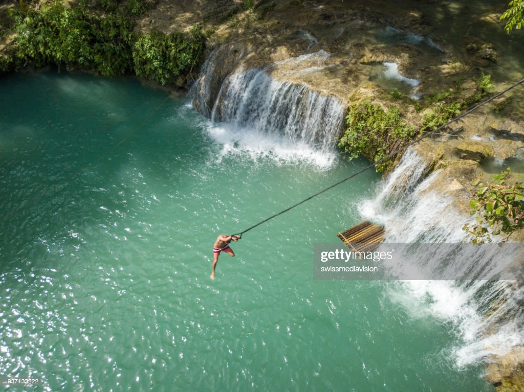 Drone point of view of man jumping into waterfall pool : Stock Photo