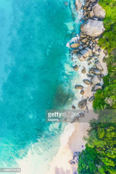 drone point of view of the beach of mahe, baie carana, seychelles. - lagoon stock pictures, royalty-free photos & images