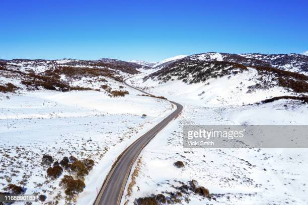drone point of view over the snow fields and long winding road up the mountain in australia - snowcapped mountain stock pictures, royalty-free photos & images