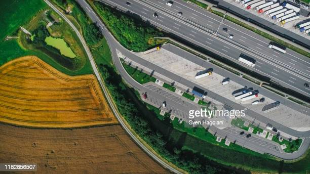 drone point of view semi-trucks parked at truck stop between highway and farmland, bayern, germany - bayern stock pictures, royalty-free photos & images