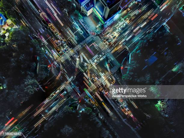 drone point view of city street crossing at rush hour - illuminated stock pictures, royalty-free photos & images