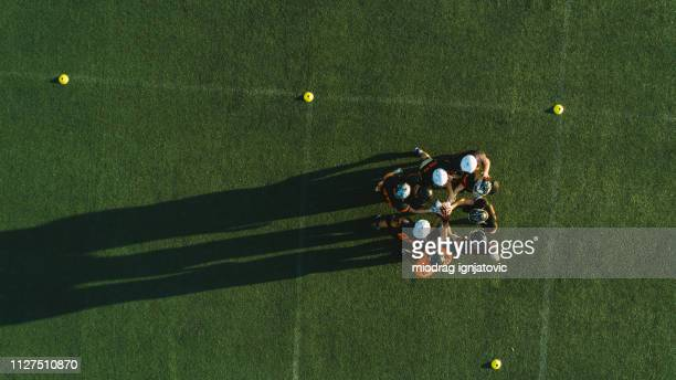 drone point view of players huddling - american football sport stock pictures, royalty-free photos & images