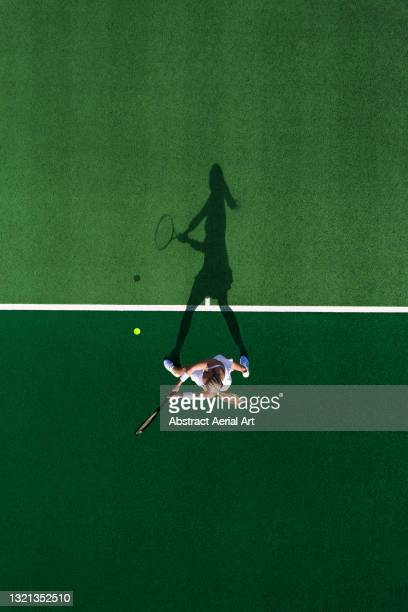 drone shot above a female tennis player and her shadow, england, united kingdom - drone point of view stock pictures, royalty-free photos & images