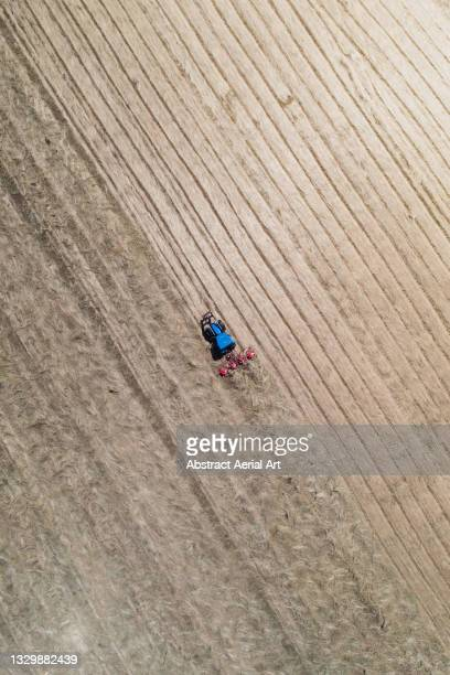 drone shot above a tractor cutting a field, cornwall, england, united kingdom - elevated view stock pictures, royalty-free photos & images