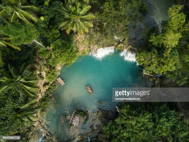 drone shot aerial view of young woman bamboo rafting at tropical waterfall - falling water stock photos and pictures