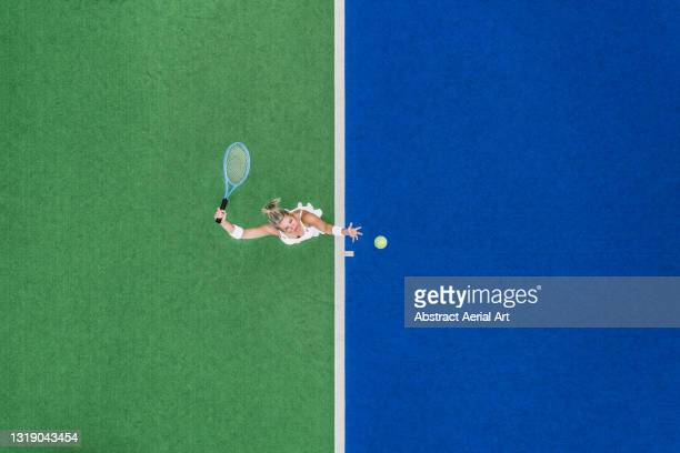 drone shot looking down on a female about to hit a tennis serve on a two-toned, astroturf, tennis court, england, united kingdom - match sport stock pictures, royalty-free photos & images