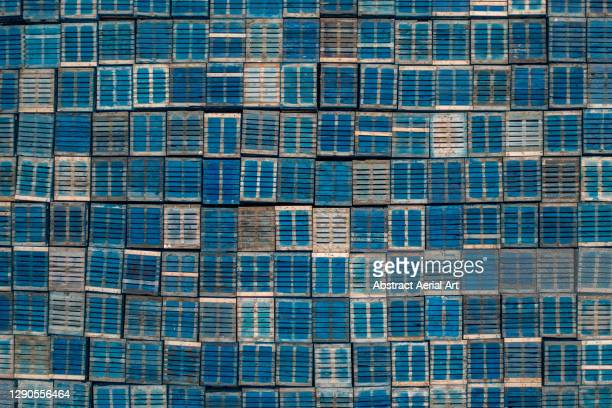 drone shot looking down on a stack of blue coloured pallets, england, united kingdom - pallet industrial equipment stock pictures, royalty-free photos & images