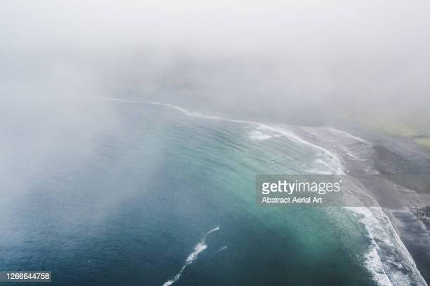 drone shot looking through low level clouds at a bay and a black sand beach, isle of skye, scotland, united kingdom - geology stock pictures, royalty-free photos & images