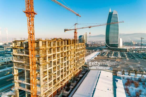 冬の日の間にバック グラウンドで企業の超高層ビルの建設現場のクレーンのドローン ショット