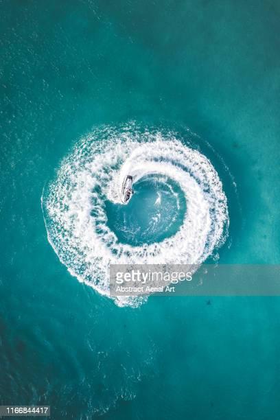 Drone shot of a jet ski making circle patterns at sea, Barbados