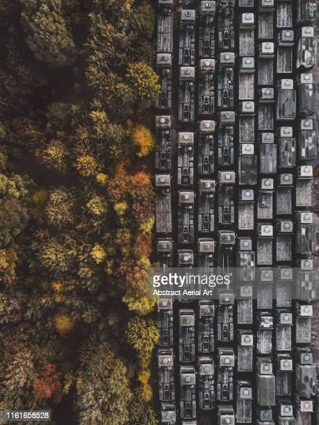 drone shot of abandoned trucks resting alongside autumn trees, united kingdom - climate change stock pictures, royalty-free photos & images