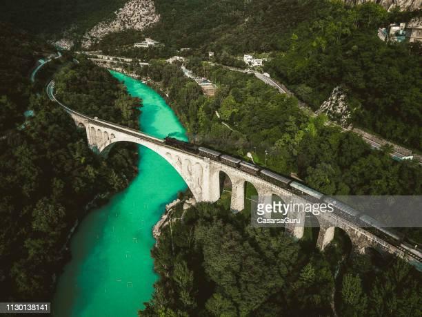 drohne schuss des historischen alten zug vorbei solkan steinbrücke über soča fluss - slowenien stock-fotos und bilder