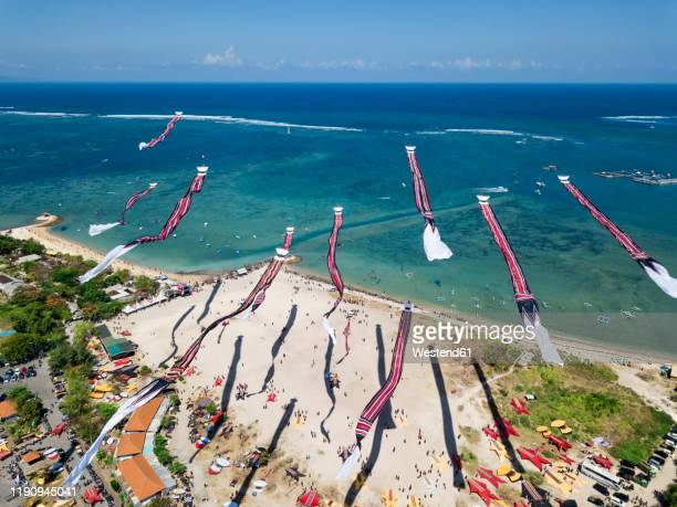 drone shot of kites flying over beach against blue sky during festival, bali, indonesia - kite toy stock pictures, royalty-free photos & images