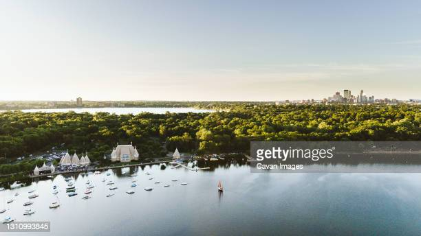 drone shot of lake harriet with the minneapolis skyline - minnesota stock-fotos und bilder