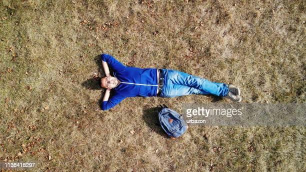 drohnenschuss des mannes auf dem feld - liegen stock-fotos und bilder