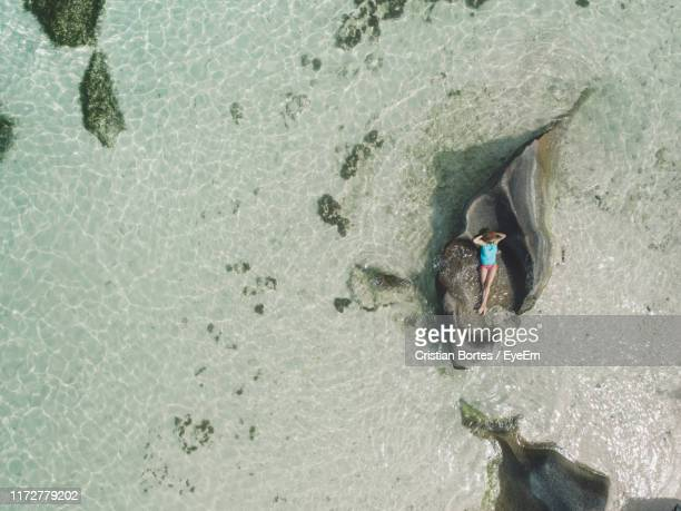 drone shot of woman relaxing on rock at beach - bortes stockfoto's en -beelden