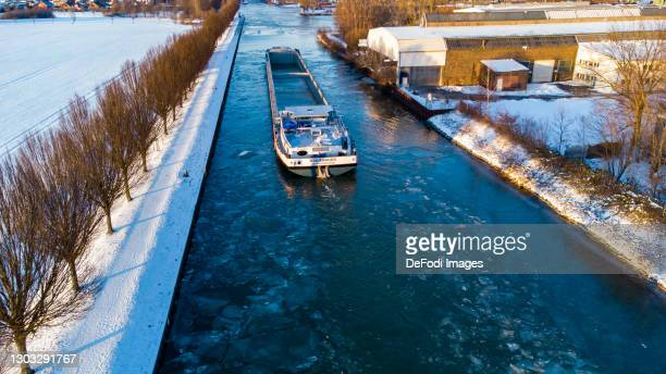 Drone shot over the Dortmund-Ems Canal in snow with a boat on the half-frozen canal on February 12, 2021 in Dortmund, Germany.