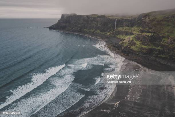drone shot showing a black sand beach and a waterfall flowing off a cliff at the edge of the atlantic ocean, isle of skye, scotland, united kingdom - dramatic landscape stock pictures, royalty-free photos & images
