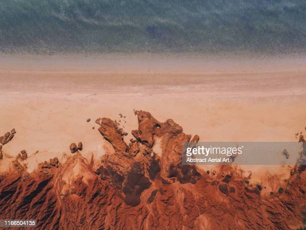 drone shot showing majestic rock formations, a beach and the ocean, james price point, the kimberley, australia - art stock pictures, royalty-free photos & images