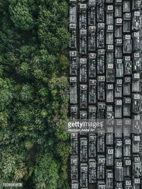 drone shot showing rows of abandoned trucks at the edge of a forest, england, united kingdom - two tone color stock pictures, royalty-free photos & images
