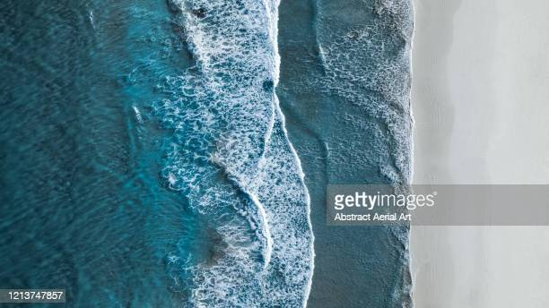 drone shot showing waves rolling onto a beach, esperance, australia - antarctic ocean stock pictures, royalty-free photos & images