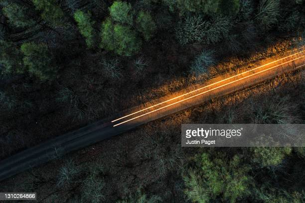 drone view above a road through a forest at night - direction stock pictures, royalty-free photos & images