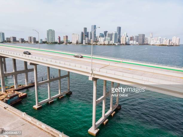 drone view from the rickenbacker causeway with traffic and the miami skyline. - key biscayne stock pictures, royalty-free photos & images