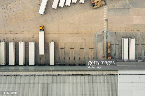drone view of a distribution warehouse with articulated lorries loading - abstract stock pictures, royalty-free photos & images