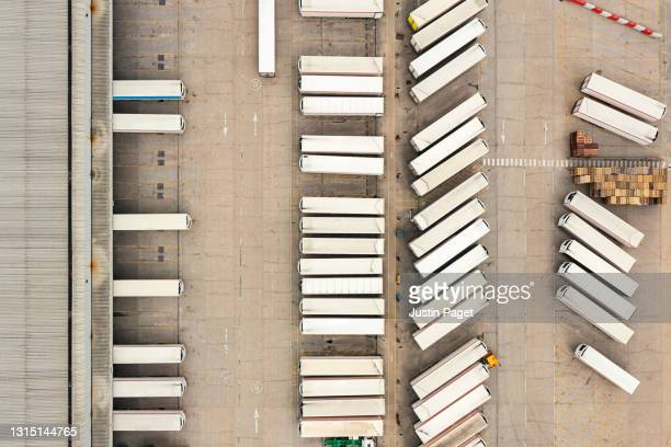 drone view of a distribution warehouse with articulated lorries loading - industrial district stock pictures, royalty-free photos & images